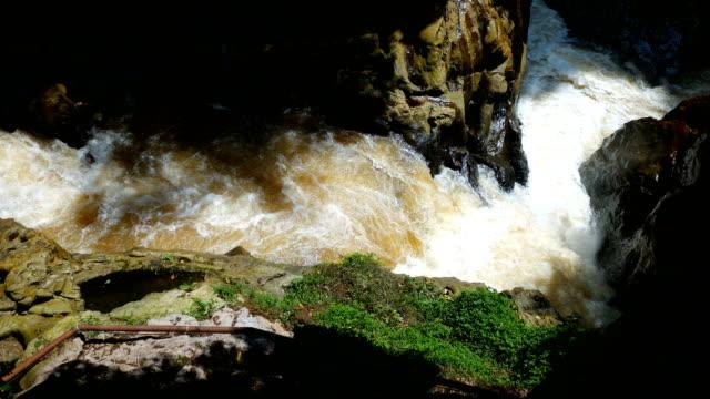 stream of river into a cave - sottosuolo video stock e b–roll