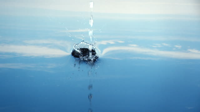 a stream of water leaves ripples and bubbles reflected in a blue sky.  - 40 o più secondi video stock e b–roll