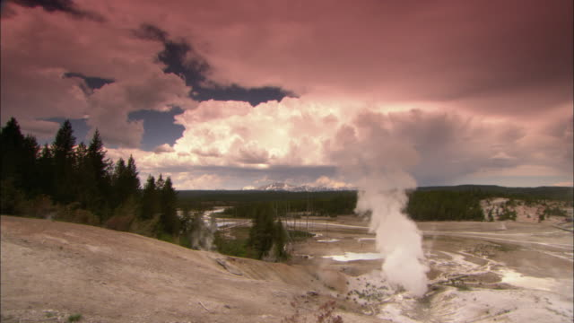 ws pan stream raising from geyser with green algae in barren landscape under overcast sky in yellowstone national park / wyoming, usa - geyser stock videos & royalty-free footage