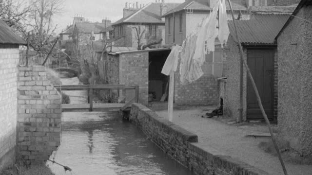vídeos de stock, filmes e b-roll de montage stream running behind row of houses, bricklayer building drainage system for house, and wastewater being carried away / united kingdom - drenagem