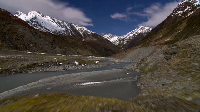A stream runs through the Remarkables near Queenstown, New Zealand. Available in HD.