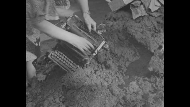 stockvideo's en b-roll-footage met stream shovel picking up and dumping mud into dump truck / car buried in mud and debris / damaged car being pulled out of mud / men digging up mud on... - drinking health 1930 film