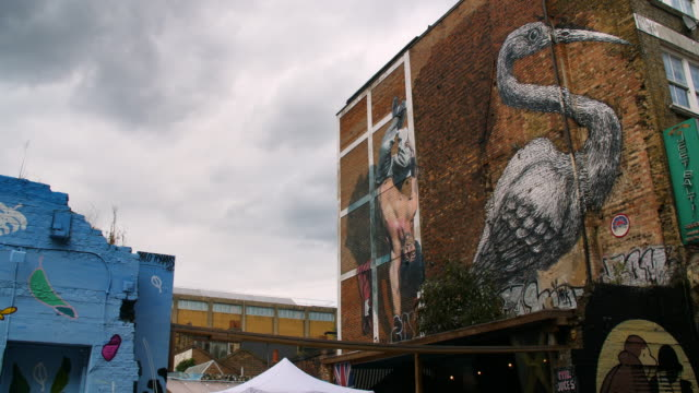 street art by roa and martin ron adorn the side of a building on hanbury street - poster stock videos & royalty-free footage