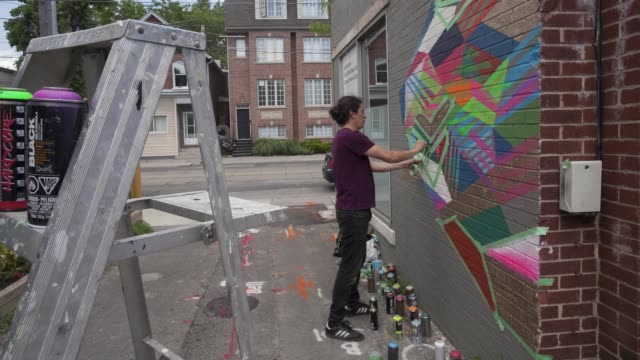 street artist decorates office wall timelapse in toronto ontario canada on june 24 2017 - painting art product stock videos & royalty-free footage