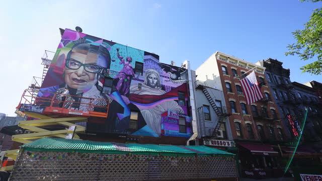 street artist elle creates a mural of the late u.s. supreme court justice ruth bader ginsburg on the building wall in east village at new york city... - 光栄点の映像素材/bロール
