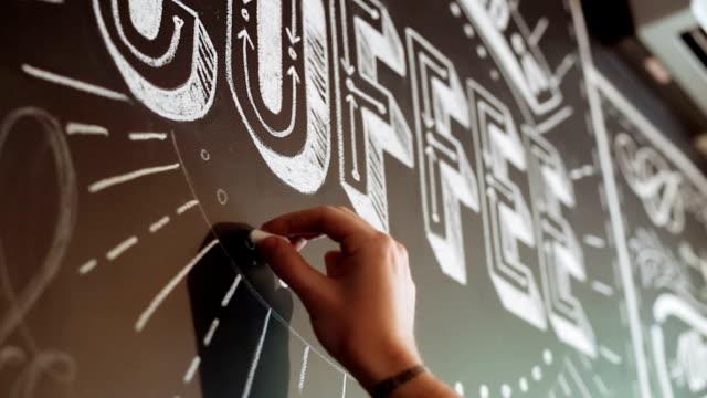 ストリート アーティストがカフェで黒塀のチョークの落書きをしています。 - チョークの跡点の映像素材/bロール