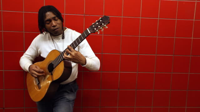 vidéos et rushes de street artist leans against red tile wall and plays acoustic guitar in urban subway station - musicien