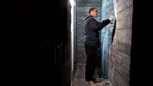 vídeos de stock, filmes e b-roll de artista de rua fazendo um graffiti na parede - pintor artista