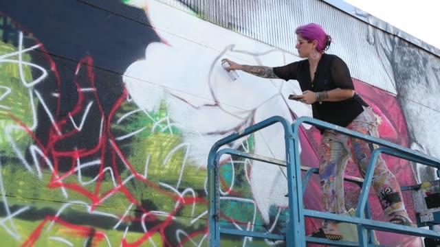 street artist, nicole 'nico' holderbaum uses spray paints to create her art on the side of a building as the wynwood neighborhood prepares for the... - joe 03 stock videos & royalty-free footage