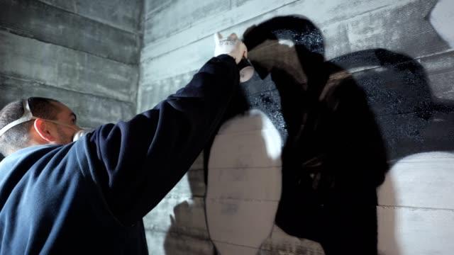 vídeos de stock, filmes e b-roll de artista de rua pintando um graffiti na parede dentro de casa - pintor artista