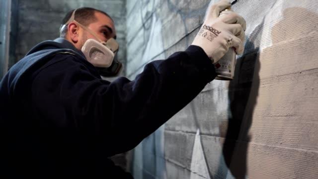 vídeos de stock, filmes e b-roll de artista de rua, com uma máscara protetora pintar um graffiti - pintor artista