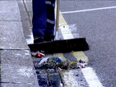 Street cleaner brushes rubbish into pile along kerb London