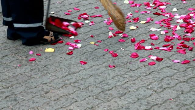 stockvideo's en b-roll-footage met straat reiniger vegen rozenblaadjes - handen in een kommetje