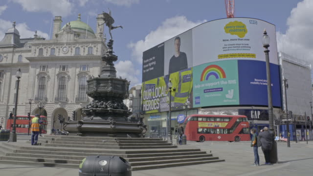 a street cleaner works at piccadilly circus street as nhs messages on the large led billboards are projected during the coronavirus pandemic on may... - distant stock videos & royalty-free footage
