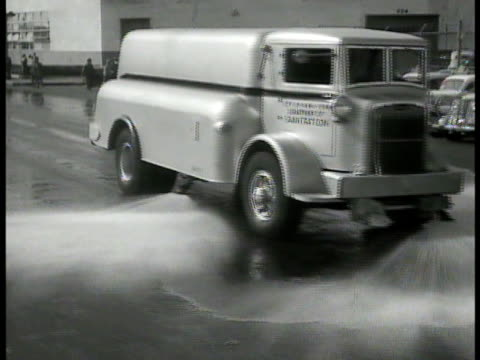 street cleaning truck spraying water on street people shopping indoor flea market nypd policeman directing traffic gesturing w/ single white gloved... - water flea stock videos and b-roll footage