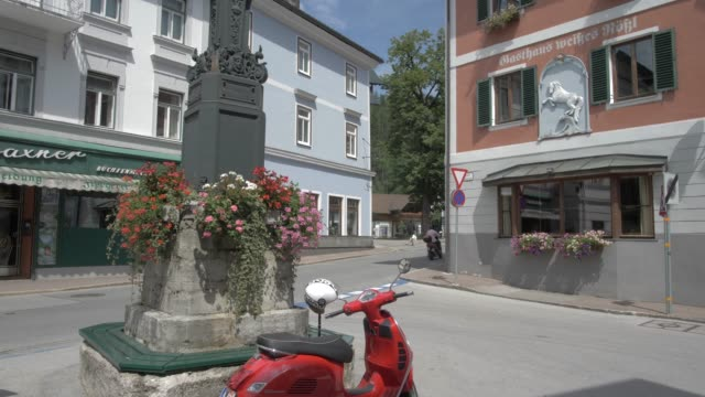 street, clock and buildings in bad aussee, styria, austrian alps, austria, europe - スクーター点の映像素材/bロール