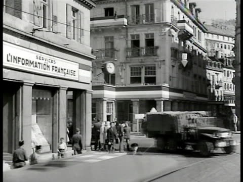 vídeos de stock, filmes e b-roll de street corner in germany, french & german pedestrians. crowd waiting for trolley. crowd entering butcher shop. crowd pushing, trying to get in. int... - 1946