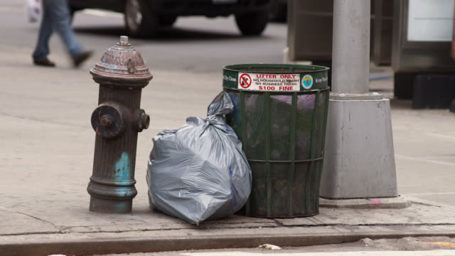 a street corner with a fire hydrant as well as trash bag and garbage in new york - fire hydrant stock videos & royalty-free footage
