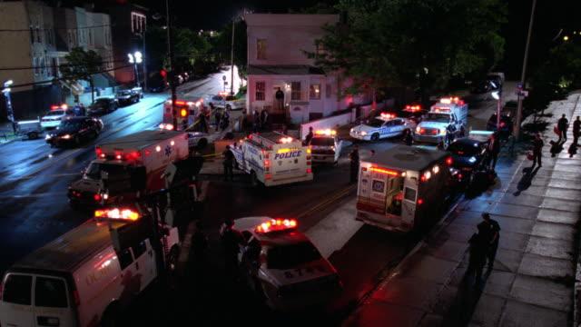 MS ZI Street corner with police cars and ambulance vehicles, siren lights flashing. looks like a crime scene