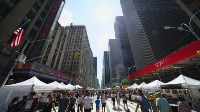 street fair was opened on 6th avenue between 42nd street and 57th street manhattan new york on aug. 19 2017. people walk down among the many shopping booths and food venders along the both side of 6th avenue skyscrapers. - high density population stock videos and b-roll footage