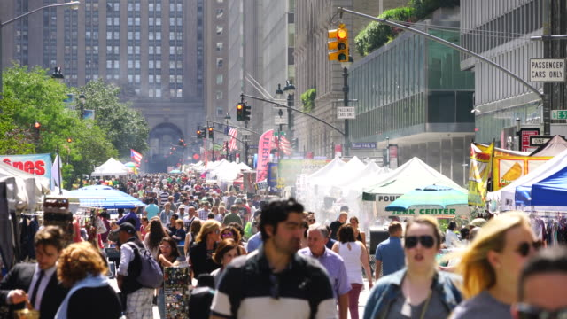 street fair was opened on park avenue between 45th street and 57th street midtown manhattan new york on aug. 27 2017. people walk down among the many shopping booths and food venders along the park avenue. city traffic crosses among the crowded avenue. - street name sign stock-videos und b-roll-filmmaterial