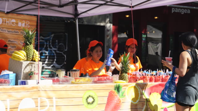 Street Fair was opened on the 2nd Avenue at East Village Manhattan New York on Jul. 16 2017. Women sell fresh fruits juice at stand.