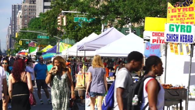 street fair was opened on the 2nd avenue at east village manhattan new york on jul. 16 2017. people walks down the 2nd avenue among the many street shops along the street. - exhibition stock videos & royalty-free footage