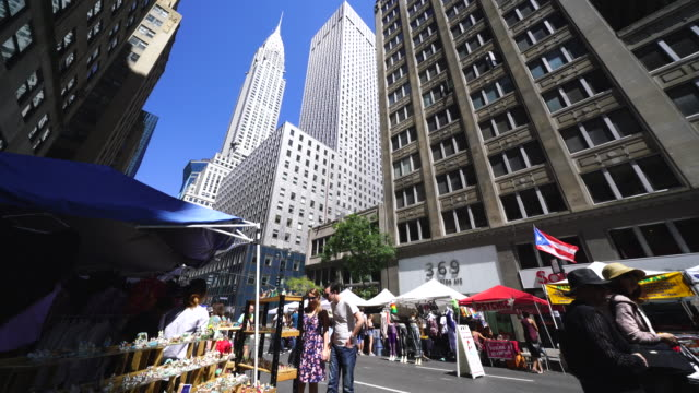Street Fair was opened on the Lexington Avenue at Midtown Manhattan New York on Jul. 30. People walk down the Lexington Avenue among the many street shops along the street. Chrysler Building and the other skyscrapers can be seen behind.