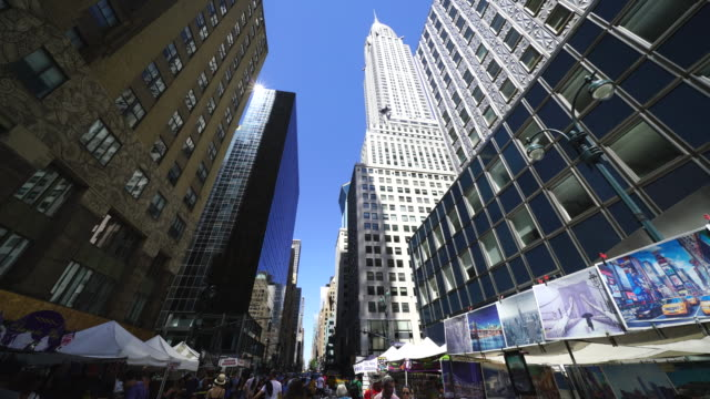 street fair was opened on the lexington avenue at midtown manhattan new york on jul. 30. people walk down the lexington avenue among the many street shops along the street. chrysler building and the other skyscrapers can be seen behind. - other stock videos & royalty-free footage