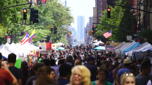 street fair was opened on the lexington avenue at midtown manhattan new york on jul. 30 2017. crowd walks down the lexington avenue among the many street shops along the tree lined street. rows of midtown buildings can be seen behind. - mässa utställning bildbanksvideor och videomaterial från bakom kulisserna