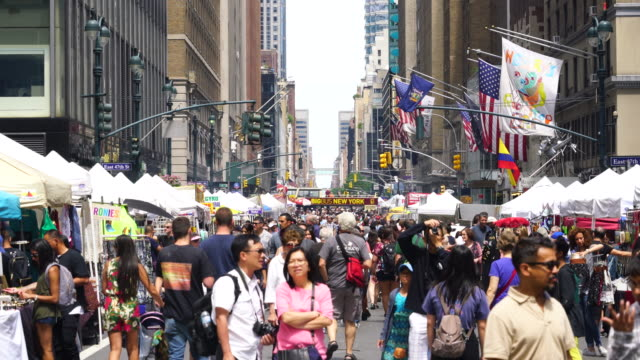 Street Fair was opened on the Lexington Avenue at Midtown Manhattan New York on Aug. 06 2017. Crowd walks down the Lexington Avenue among the many street shops along the street. Rows of Midtown buildings can be seen behind.