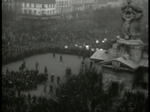 vidéos et rushes de street filled w/ people walking forward gendarmes watching from side male on top of statue waving communist flag french army on horseback walking... - 1934