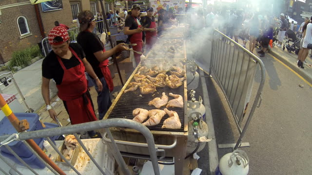 charcoal cooking chicken in salsa on saint clair avenue west festival which is the largest hispanic or latin event in canada. this year one of the... - ちやほや点の映像素材/bロール