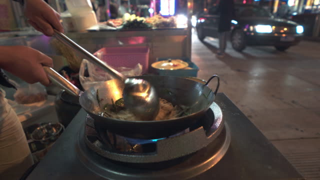 Street food cooking on a wok at night
