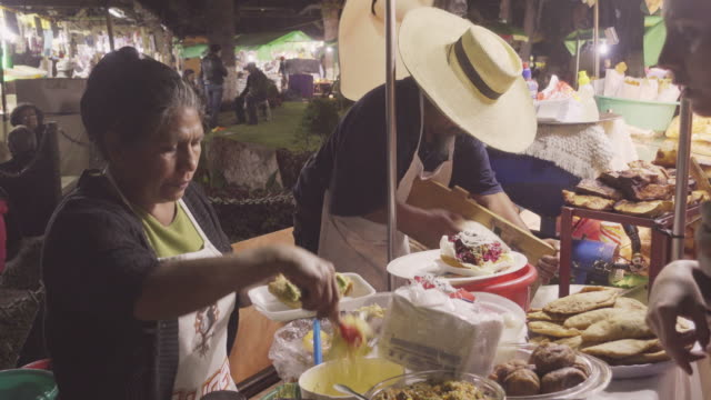 Street food market at Antigua Guatemala. Hispanic women cooking guacamole and tortilla wrap roll