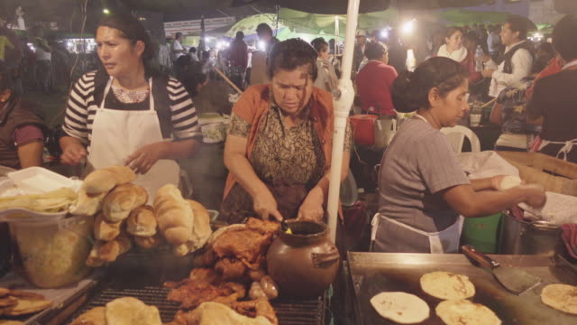 street food market at antigua guatemala. hispanic women cooking grilled meat and tortilla wrap roll - guatemala stock videos & royalty-free footage