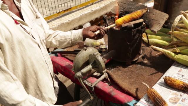 vídeos de stock, filmes e b-roll de street hawker roasting corn cob on a stove, rishikesh, uttarakhand, india - rishikesh