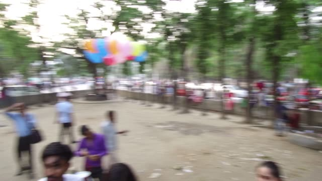 A street hawker sells balloon while Prachyanat School of Acting and Design take out a procession Lal Jatra to remember making the genocide by...