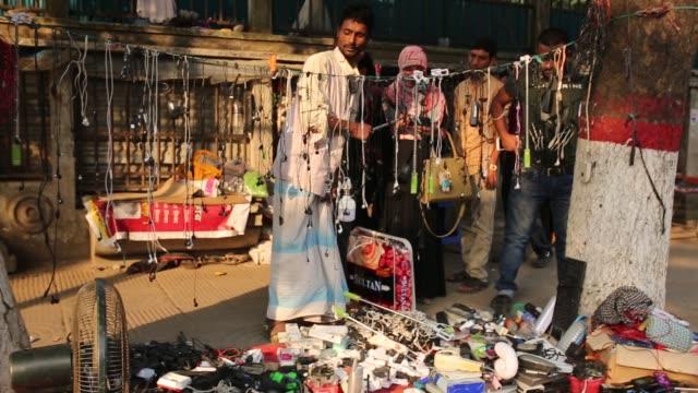 a street hawker sells used cell phones at a makeshift market in dhaka - un giorno nella vita video stock e b–roll