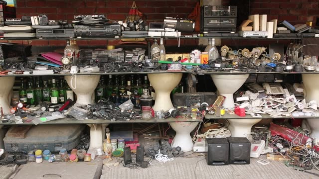 A street hawker sells used waste electronic product at a makeshift market in Dhaka