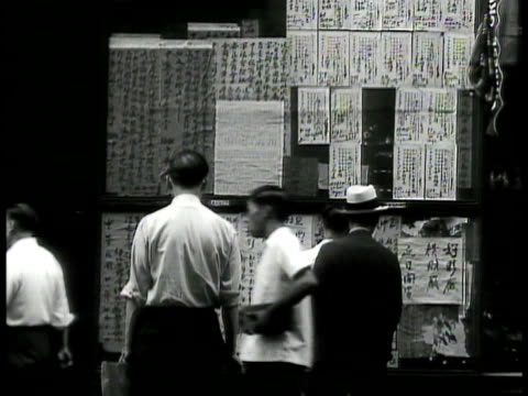 vídeos y material grabado en eventos de stock de street in chinatown. men reading postings on wall. chinese restaurant signs. little italy: italian restaurant sign. people in parade carry statue of... - 1930 1939