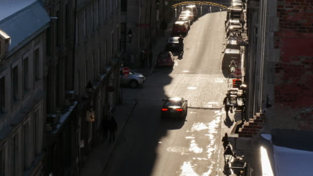 street in old montreal seen from above with sun reflections on cars - vieux montréal stock-videos und b-roll-filmmaterial