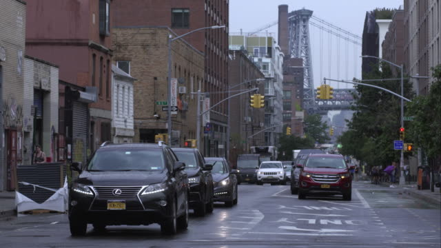 vídeos de stock, filmes e b-roll de street intersection in brooklyn on a rainy day with view of williamsburg bridge in background. - williamsburg new york