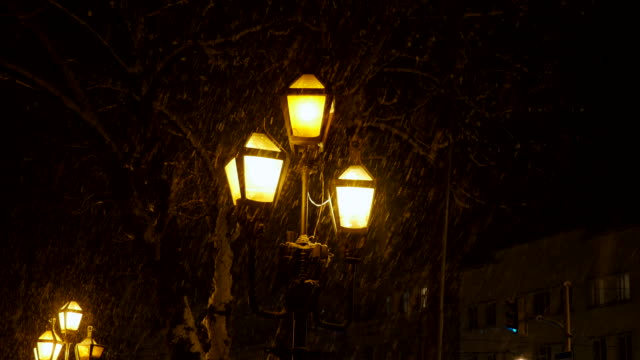 street lamp and falling snow at night in the city