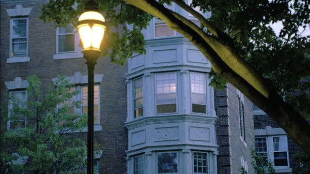 "a street lamp glows across from the ""fitler commons"" apartment building. - bay window stock videos & royalty-free footage"