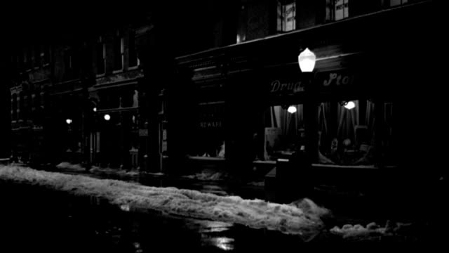 street lamps glow outside shops on a snowy street. - 1949 stock videos & royalty-free footage