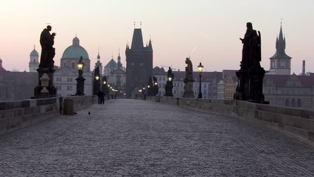 ms street lamps shut down at charles bridge at early morning / prague, hlavni mesto praha, czech republic - charles bridge stock-videos und b-roll-filmmaterial