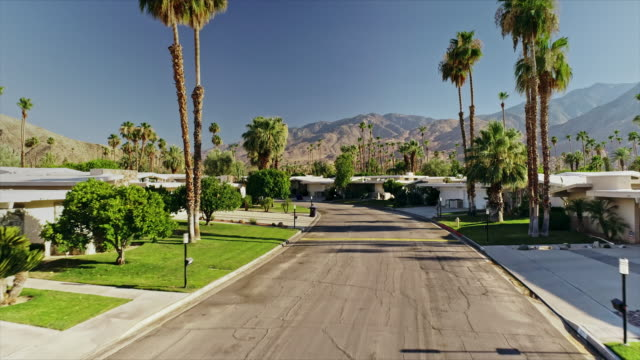 ws street level aerial of residential street with 1960s mid-century modern homes in historic canyon estates neighborhood and san jacinto mountains in far distance - 1950 stock videos & royalty-free footage