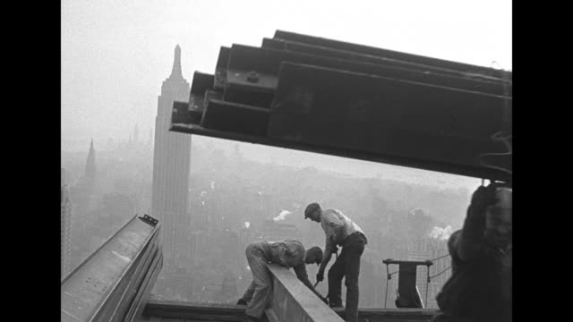 street level view of the tower with pan up / looking down on construction workers with steel girders and street far below / vs girders being lifted... - rockefeller center video stock e b–roll