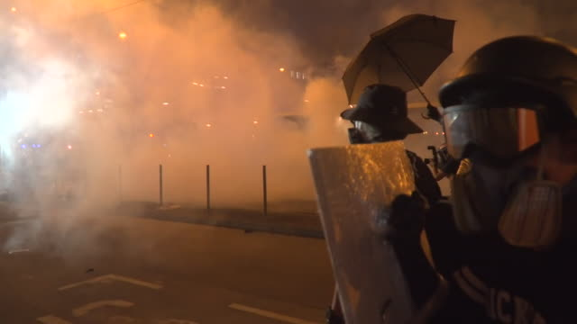 street level view of violent clashes in hong kong - demonstrant stock-videos und b-roll-filmmaterial